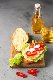 Sandwich croissant freschi con pollo grigliato, peperone, salsa e foglie di insalata con succo
