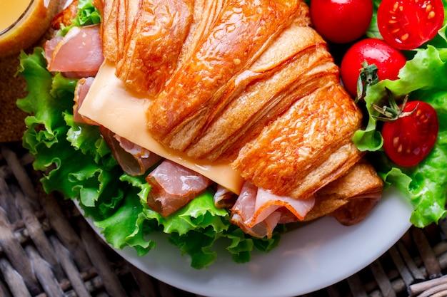 Sandwich croissant freschi con prosciutto, formaggio, pomodorini