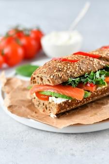 Sandwich di avocado, salmone, crema di formaggio, pomodori e foglie di lattuga