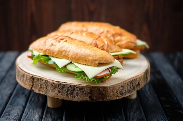 Sandwich di cacciatore con prosciutto, cetriolo, formaggio cheddar su tavola di legno (foto con profondità di campo)