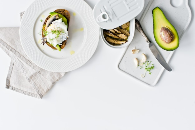 Sandwich di pane nero con avocado, uovo in camicia e spratti.