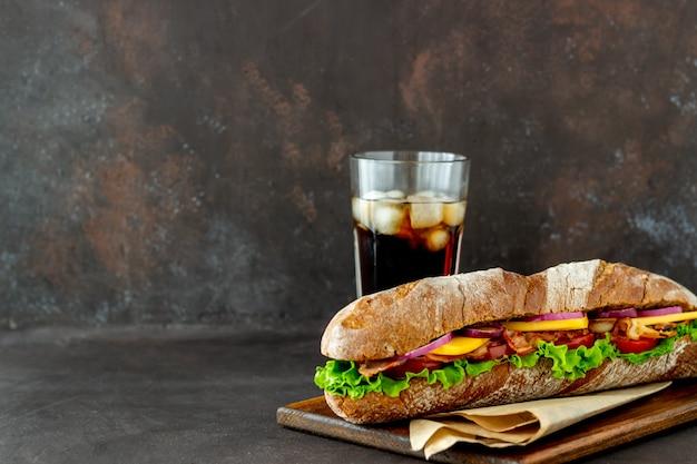 Sandwich di pane nero con insalata, pancetta, pomodori, formaggio e cipolle. prima colazione. fast food.