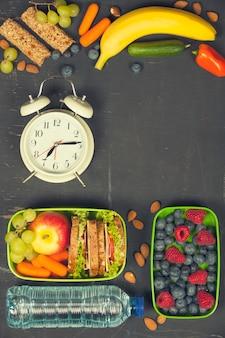 Sandwich, mela, uva, carota, bacche in scatole di plastica per il pranzo, al