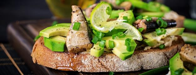 Sandwich - smorrebrod con spratti, avocado e crema di formaggio su tavola di legno.