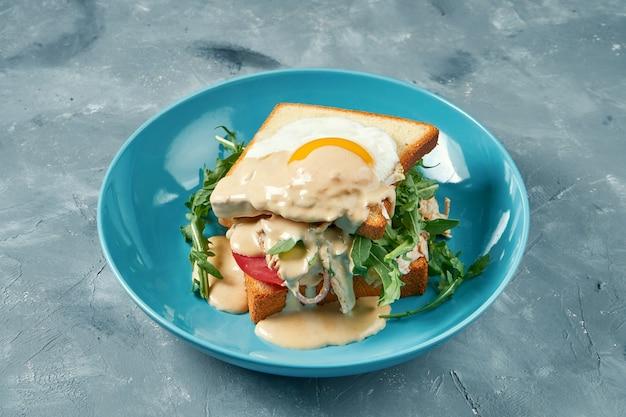 Sandwich succoso con tacchino, uova strapazzate e salsa olandese in un piatto blu
