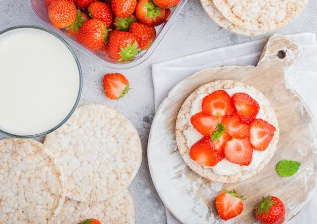 Sane torte di riso biologiche con ricotta e fragole fresche e bicchiere di latte
