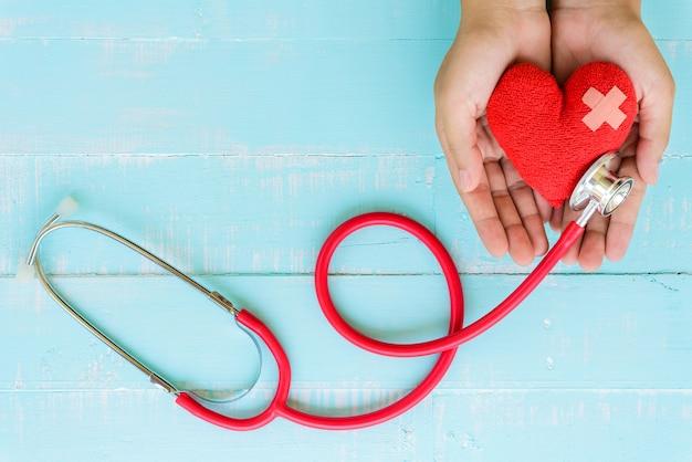 Sanità e concetto medico. mano della donna che tiene cuore rosso con lo stetoscopio