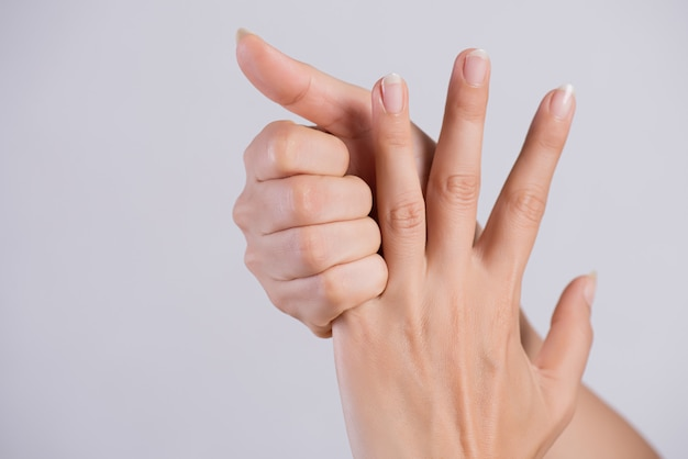 Sanità e medicina. donna che massaggia il suo dito indice doloroso.