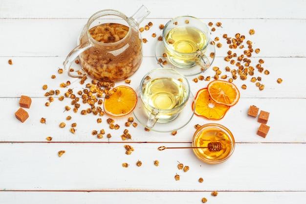 Sano camomilla in tazza di vetro. teiera, vasetto di miele