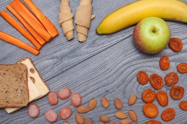 Sano pranzo scolastico con sandwich con formaggio, mela, banana, mandorle, frutta secca, acqua, caramelle naturali, carota, biscotti copia spazio, piatto, vista dall'alto.