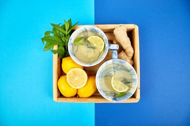 Sano tè due tazze con limone, zenzero, menta