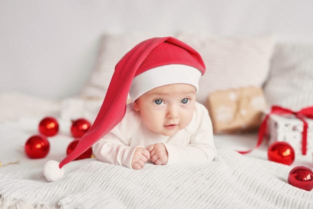 Santa bambino con una decorazione di capodanno su una luce