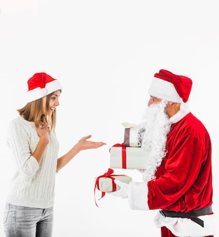 Santa claus che dà il contenitore di regalo alla giovane donna