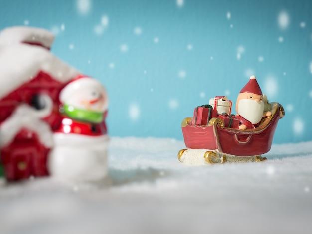Santa claus felice con il contenitore di regali sulla slitta di neve che va alla casa della neve.