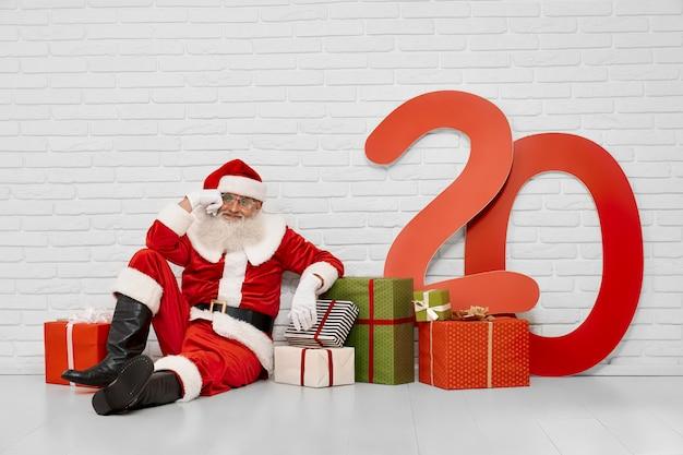 Santa claus premurosa che si siede sul pavimento con i contenitori di regalo