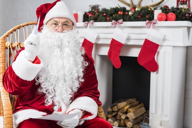 Santa seduto in poltrona con lista dei desideri e penna