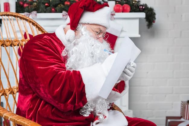 Santa seduto in poltrona e leggere la lista dei desideri