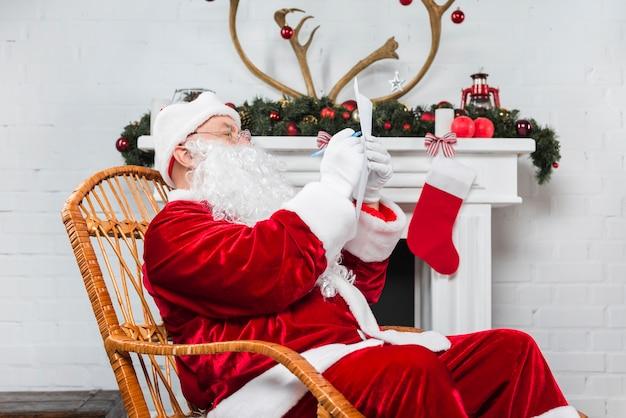 Santa seduto in sedia a dondolo con carta e penna