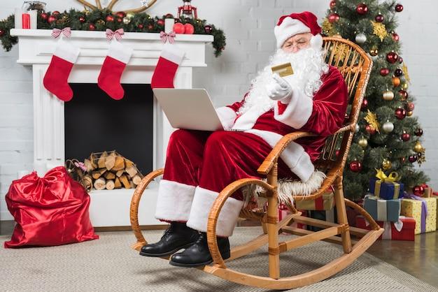 Santa seduto sulla sedia a dondolo con computer portatile
