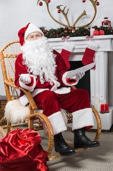 Santa seduto sulla sedia a dondolo con la lista dei desideri