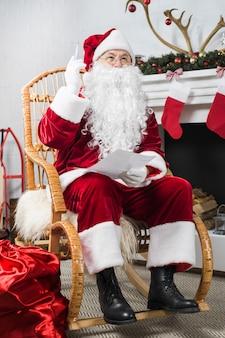 Santa seduto sulla sedia a dondolo con lista dei desideri e penna