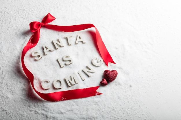 Santa sta arrivando testo e nastro rosso su sfondo innevato. natale. copyspace. tradizione cristiana delle vacanze