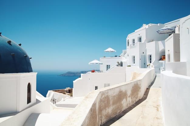 Santorini con chiesa, architettura bianca e vista sul mare in grecia, imirovigli.
