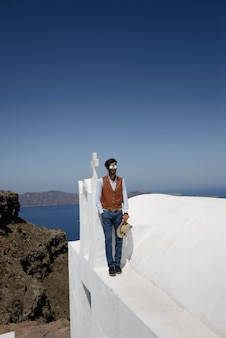 Santorini oia grecia, giovane uomo in piscina affacciata sull'oceano caldera di santorini durante le vacanze