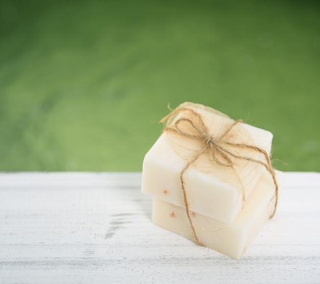 Sapone al latte della stazione termale sulla tavola di legno bianca