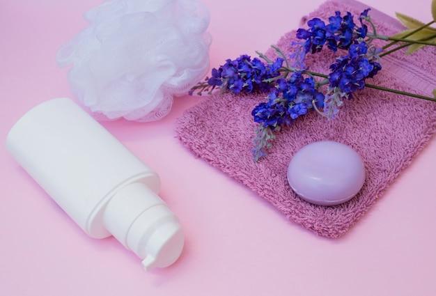 Sapone; asciugamano; fiore di lavanda; luffa e bottiglia cosmetica su sfondo rosa