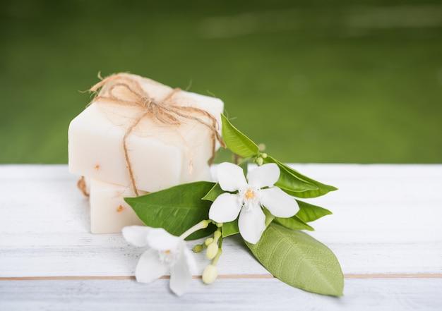 Sapone della stazione termale e piccolo fiore bianco sulla tavola di legno con fondo verde