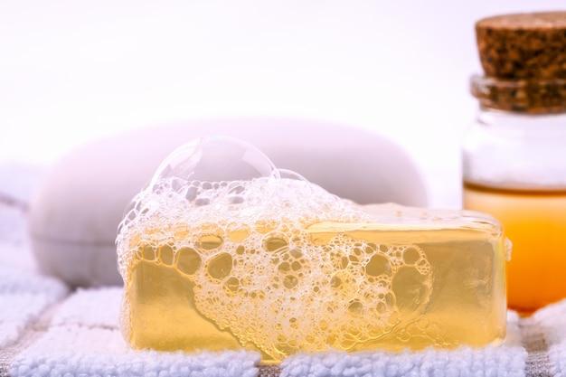 Sapone di erbe della stazione termale sull'asciugamano di bagno bianco con l'isolato del miele su fondo bianco.