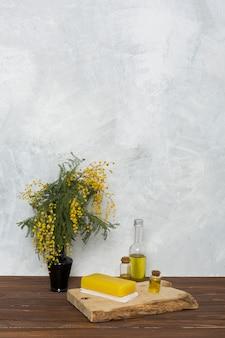 Sapone di erbe giallo sul tovagliolo piegato e bottiglia di olio essenziale vicino al vaso di fiori giallo mimosa