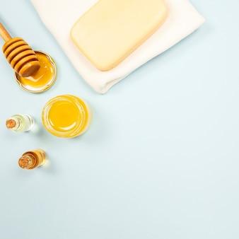 Sapone e bottiglia di olio essenziale con miele su sfondo chiaro