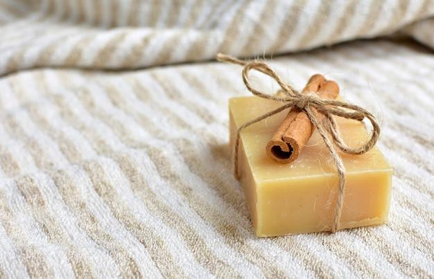 Sapone fatto a mano biologico e naturale con cannella su asciugamano di lino.