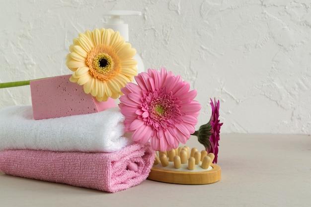 Sapone fatto a mano naturale, pezzuola per lavare e asciugamano su fondo di legno.