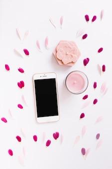Sapone floreale; candela e smartphone decorati con petali di fiori su sfondo bianco