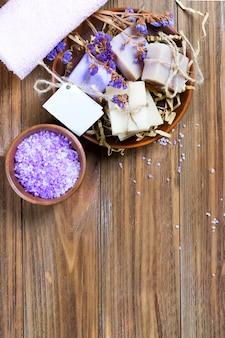 Sapone organico in un cestino con i fiori asciutti e sale marino naturale in una ciotola su una tavola di legno marrone con lo spazio della copia.