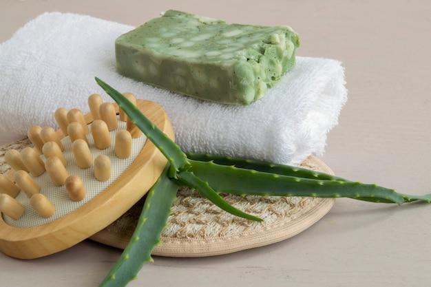 Sapone, pezzuola per lavare ed asciugamano fatti a mano naturali su fondo di legno.