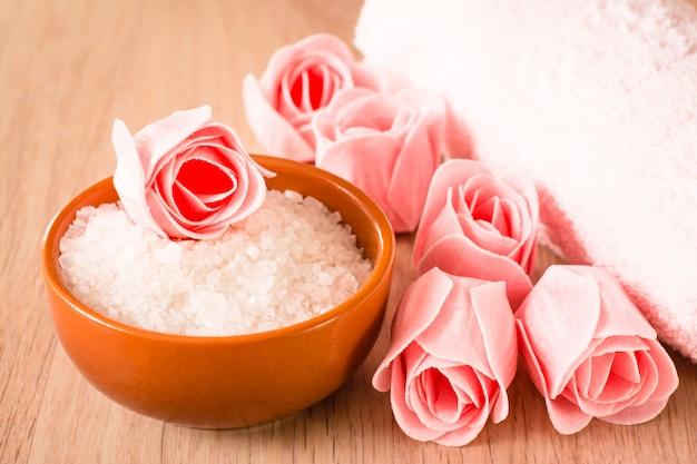 Sapone sotto forma di fiori, sale marino nella ciotola e asciugamano su un fondo di legno