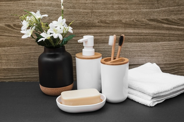 Sapone; spazzolino da denti; bottiglia cosmetica; asciugamano e vaso di fiori bianchi sulla superficie nera