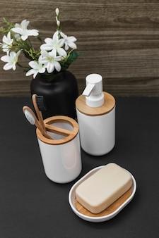 Sapone; spazzolino da denti; bottiglia cosmetica e vaso di fiori bianchi su tavolo
