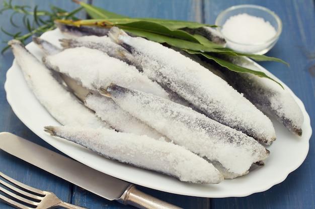 Sardine in ghiaccio sul piatto bianco su legno blu