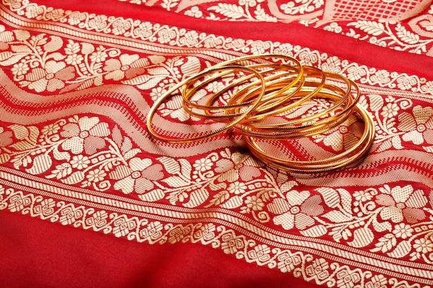 Sari indiani con bracciali d'oro