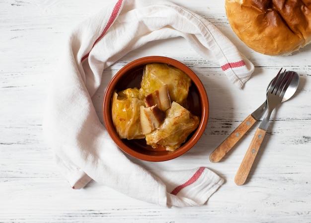 Sarma - piatto tradizionale della cucina balcanica. involtini di cavolo con carne e riso. cucina balcanica. cucina serba. sfondo in legno chiaro vista dall'alto. spazio per il testo