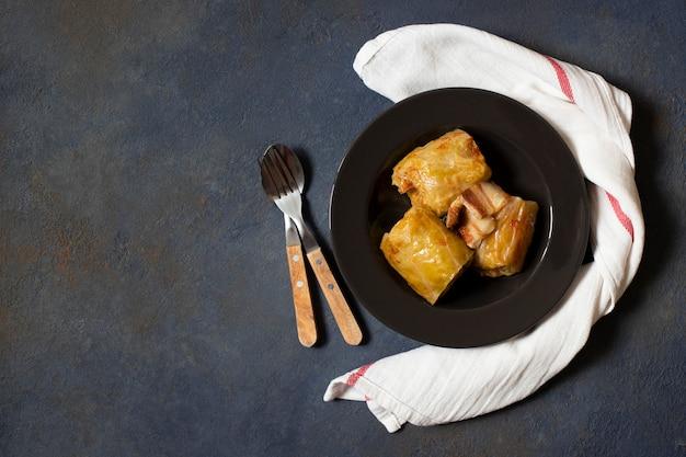 Sarma - piatto tradizionale della cucina balcanica. involtini di cavolo con carne e riso. cucina balcanica. cucina serba. sfondo scuro vista dall'alto. spazio per il testo