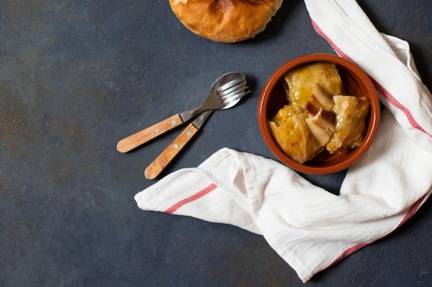 Sarma - piatto tradizionale della cucina balcanica. involtini di cavolo con carne e riso, serviti con pane. cucina balcanica. cucina serba. sfondo scuro vista dall'alto. spazio per il testo