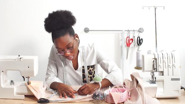 Sarta donna afro-americana, stilista impegnata nella sua attività preferita cucendo abiti nel suo laboratorio