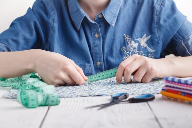 Sarta o stilista giovane donna che lavora come stilista di moda, scegli i filati per il tessuto per cucire, la professione e l'occupazione