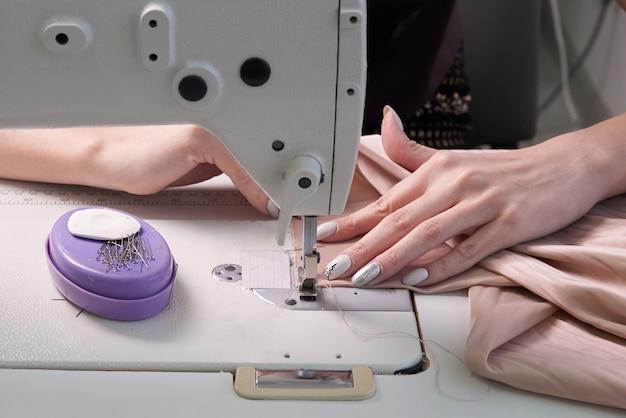 Sarta utilizzando macchina da cucire in studio su misura, moderno negozio di atelier